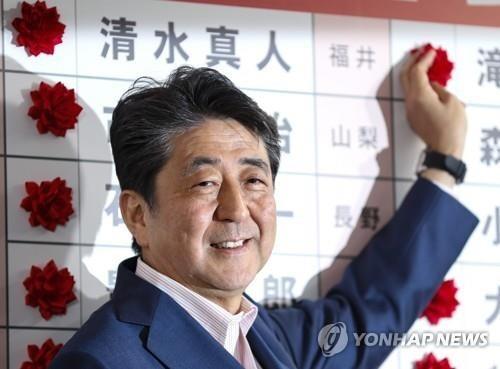 아베 신조 일본 총리가 21일 치러진 참의원 선거의 자민당 당선자 이름에 꽃을 달고 있다. [사진= EPA/연합뉴스]